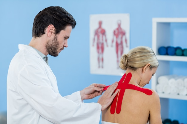 physiotherapist sticking tape on female patient
