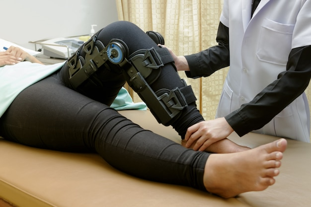Physiotherapist do stretch exercises on patient's leg, rehabilitation for knee injury
