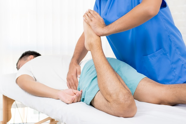 Physiotherapist stretching leg of male patient on the bed in hospital