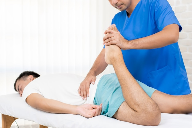 Physiotherapist stretching leg of male patient on the bed