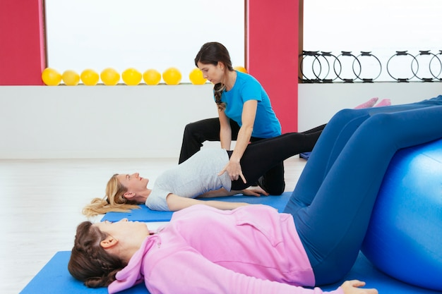 Physiotherapist teacher explaining back exercises to a future mom
