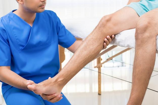 Физиотерапевт тренирует реабилитационное упражнение пациенту со сломанной ногой