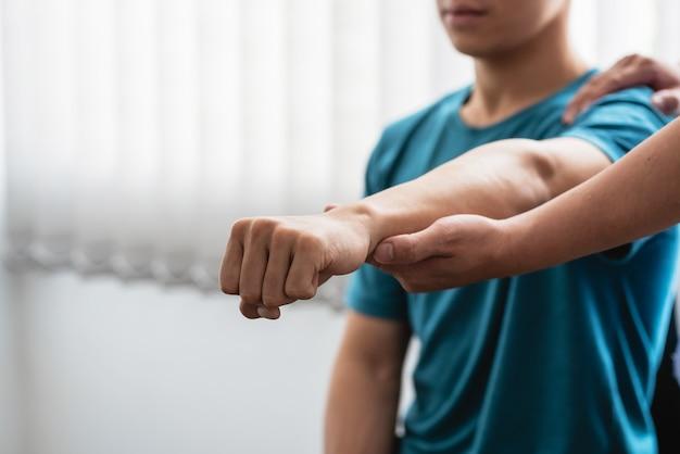 병원에서 팔꿈치 통증이 있는 남자를 치료하는 물리치료사.