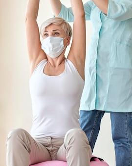 여성 환자와 치료를 받고있는 물리 치료사