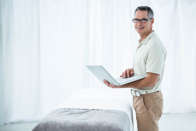 Physiotherapist using digital tablet in his clinic
