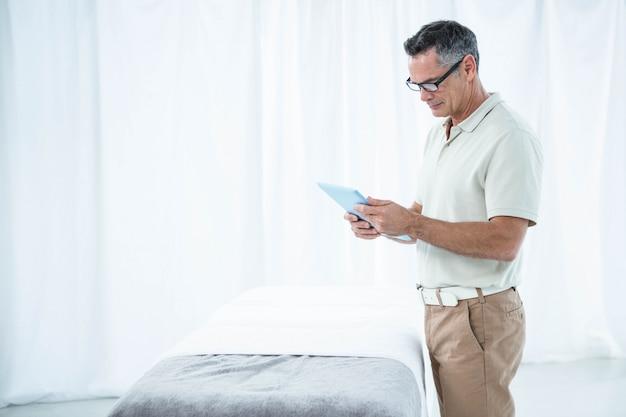 彼の診療所でデジタルタブレットを使用して理学療法士