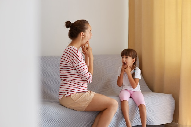Fisioterapista che indossa una camicia casual a righe che lavora su difetti del linguaggio o difficoltà con una bambina piccola a casa mentre è seduto sul divano, lezioni private per migliorare la pronuncia dei suoni.