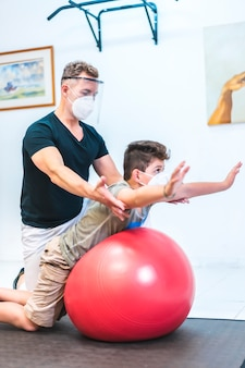 Physiotherapist with mask and screen doing back stretches to a child. opening with security measures of physiotherapists in the covid-19 pandemic. osteopathy, therapeutic chiromassage