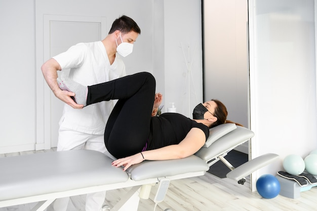 患者にマッサージを与える保護マスクを持った理学療法士。 covid-19パンデミックにおける理学療法の安全対策で再開。オステオパシー、治療用chiromassage。