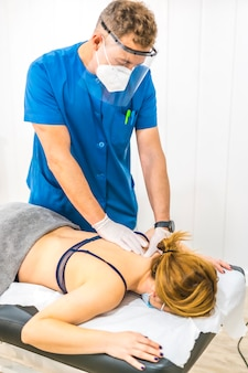 Physiotherapist with protective measures working the back of a patient. covid-19 pandemic. osteopathy, therapeutic chiromassage