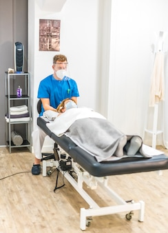 Physiotherapist with protective measures working with a patient on the stretcher, cranial osteopathy. covid-19 pandemic. osteopathy, therapeutic chiromassage
