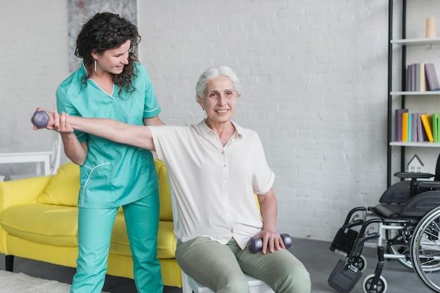 현대 클리닉에서 노인 환자와 함께 일하는 물리 요법가