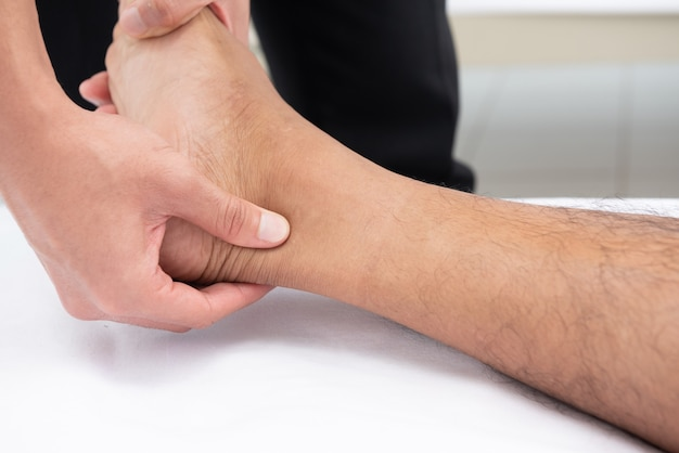 Physiotherapists use the handles in the patient's leg to lie on the bed in a medical room.