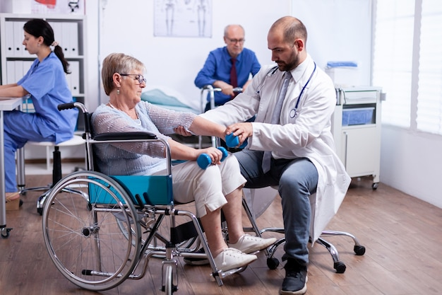 Physiotherapy for elderly woman in wheelchair to regain muscle strength in recovery clinic
