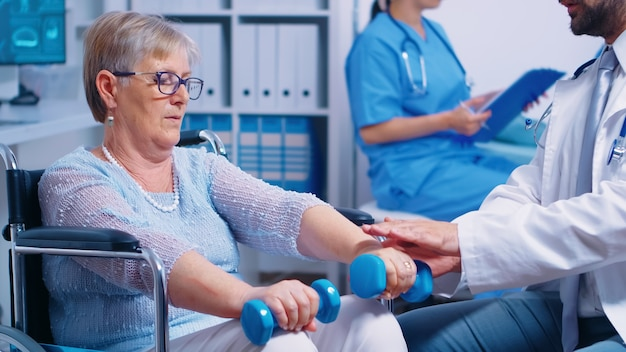 Physiotherapy for elderly woman in wheelchair, she is practicing with dumbbells to recover after a musle trauma. modern private hospital or rehabilitation clinic. lifting exercise for disabled people