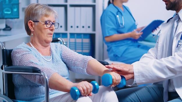 車椅子の年配の女性のための理学療法、彼女は筋肉の外傷の後で回復するためにダンベルで練習しています。現代の私立病院またはリハビリクリニック。障害者のためのリフティングエクササイズ