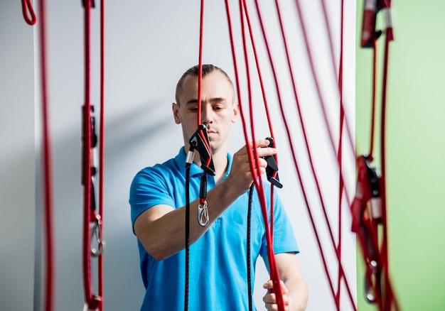 理学療法。サスペンショントレーニング療法。若い男がフィットネストラクションを行う