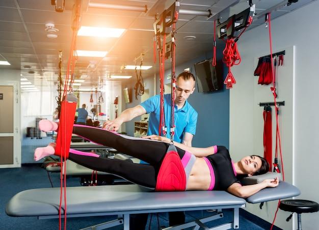 Физиотерапия. подвесная тренировочная терапия. молодая женщина делает фитнес тяги