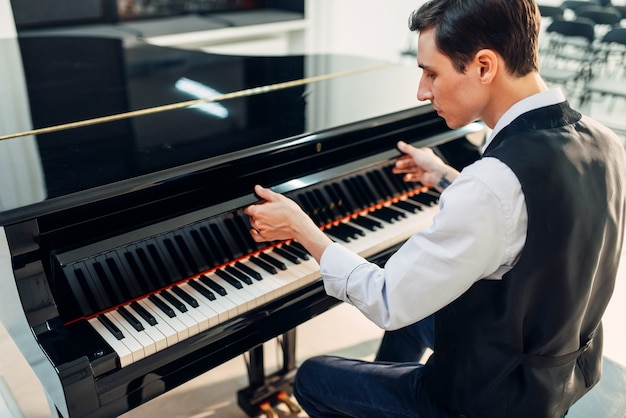Pianist opens the keyboard lid of grand piano