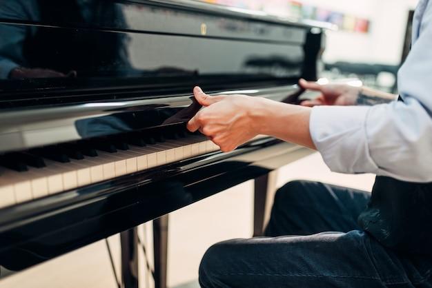 Пианист открывает крышку клавиатуры рояля