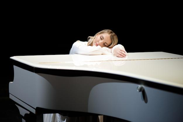 Пианист позирует возле белого пианино на сцене
