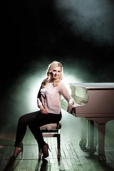 ステージ上の白いピアノの近くでポーズをとるピアニスト。