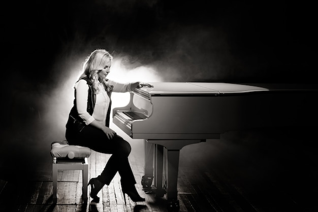 Pianist posing near white piano on the stage