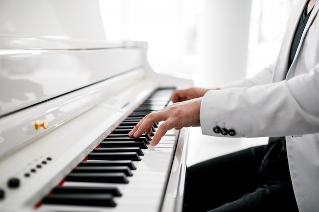 A pianist in a white suit plays the piano