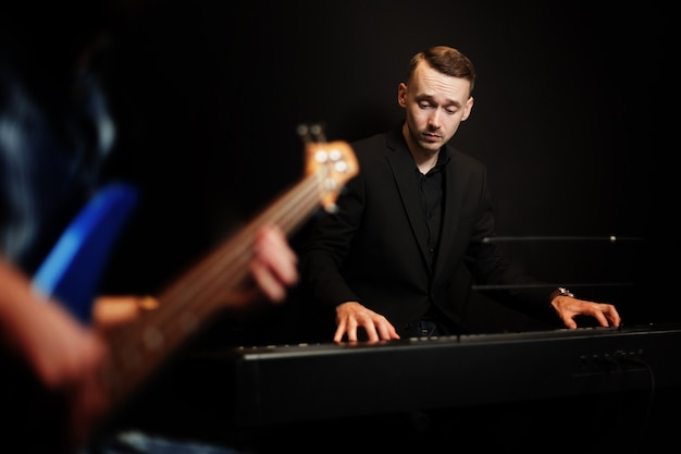Pianist with guitar in foreground