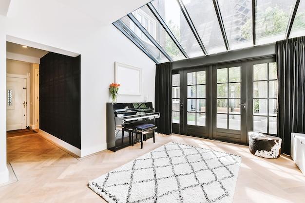유리문과 천장 창이있는 현대적인 코티지의 조명 홀에 피아노와 카펫 배치