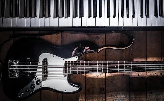 ピアノと木製の背景のクローズアップのギター