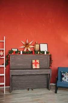Piano and christmas decor on a red wall background
