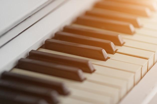 햇빛과 피아노 키보드 근접 촬영입니다. 음악과 취미 개념