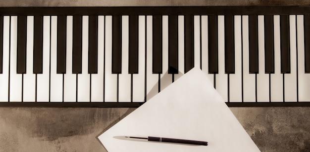 피아노 키보드, 펜 및 빈 종이입니다. 음악, 노래, 창의성, 학습을 작곡하는 개념.