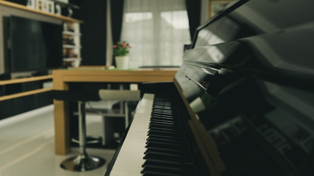 Клавиатура пианино с размытым фоном домашней гостиной с современным интерьером.