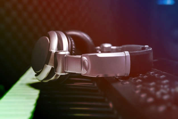 Piano keyboard with headphones for music, headphones on piano keyboard, close up,headphones on electric piano background by the music instruments background.