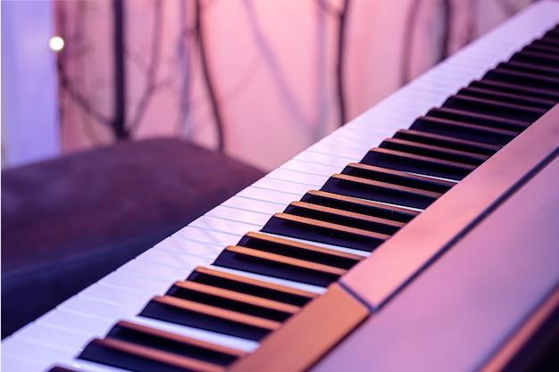 Tasti del pianoforte su un bellissimo sfondo colorato da vicino.