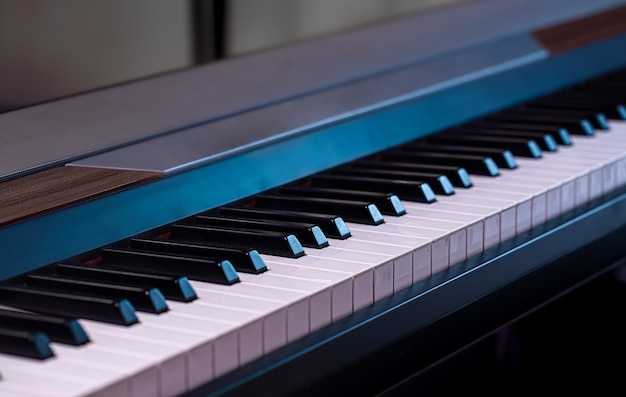Piano keys on a beautiful colored background close up.