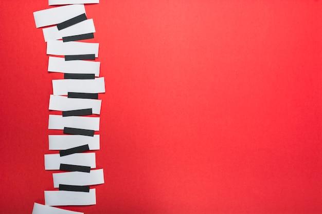 赤の背景に白と黒の紙で作られたピアノの鍵