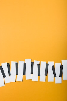 Piano keys made with black and white paper on yellow backdrop