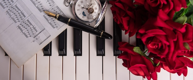 Piano keys, musical score, fountain pen, antique clock and bouquet of roses