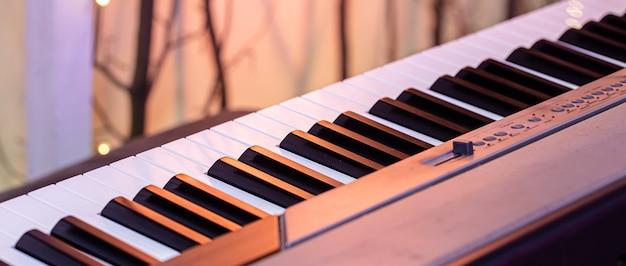 美しい色の背景にピアノの鍵盤がクローズアップ。