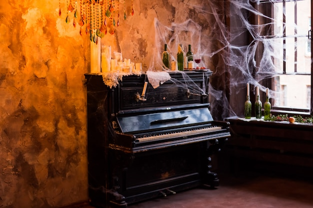 Piano standing near window. eerie cobweb covered bottles with candles and candelabras in haunted house setting. interior and decorations for halloween party. fresh ripe pomegranate, haunted house