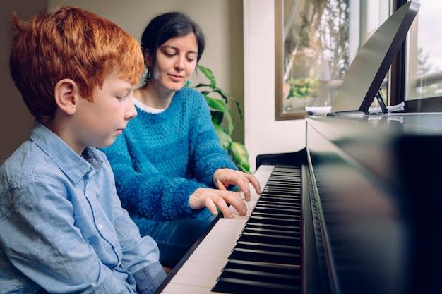 집에서 피아노 레슨을 어린 소년을 가르치는 피아노 교사 여자. 실내에서 함께 시간을 보내는 가족 생활. 음악적 미덕과 예술적 호기심을 가진 아이들. 교육적인 음악 활동.