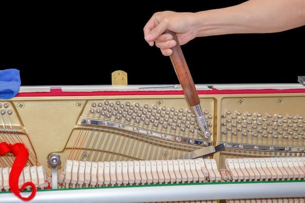 피아노 튜너 튜닝 업라이트 피아노 피아노 튜너의 오른손이 업라이트 피아노를 튜닝하고 있습니다