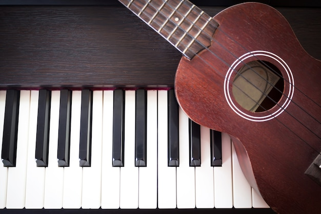 Piano with ukulele. art and music background. two kind of music instruments.