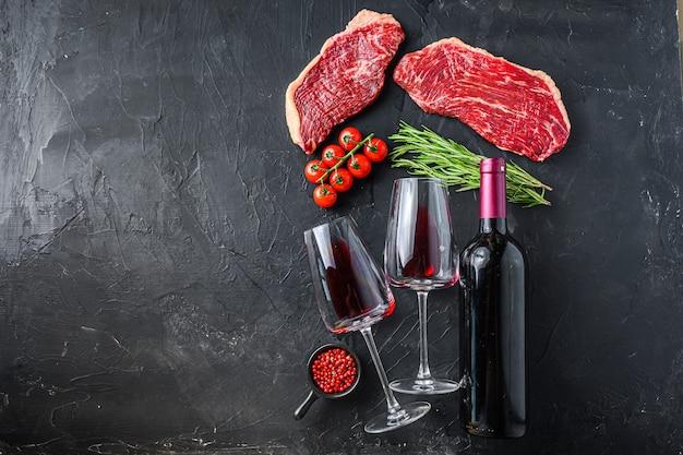 赤ワインのボトルとグラスの近くに調味料とハーブを添えたピカーニャ生ビーフステーキ