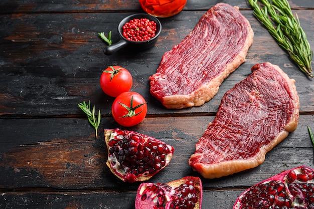 피칸하 생 유기농 쇠고기 스테이크에는 양념, 로즈마리, tpmators, 매운 칠리 오일, 석류가 오래된 어두운 나무 배경 위에 있고 텍스트를 위한 측면 공간이 있습니다.
