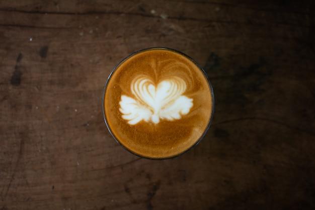 Piccolo latte art in paper cup on wooden desk