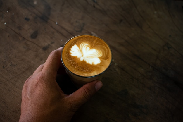 Piccolo latte art in paper cup on wooden desk
